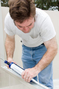Handyman using a caulking gun to caulk a window.
