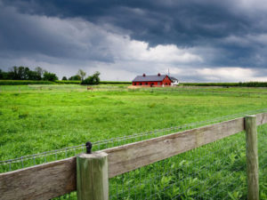 Storm clouds hovering over a farm with a fence in the foreground.